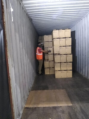Team member stocking boxes inside of a storage container.